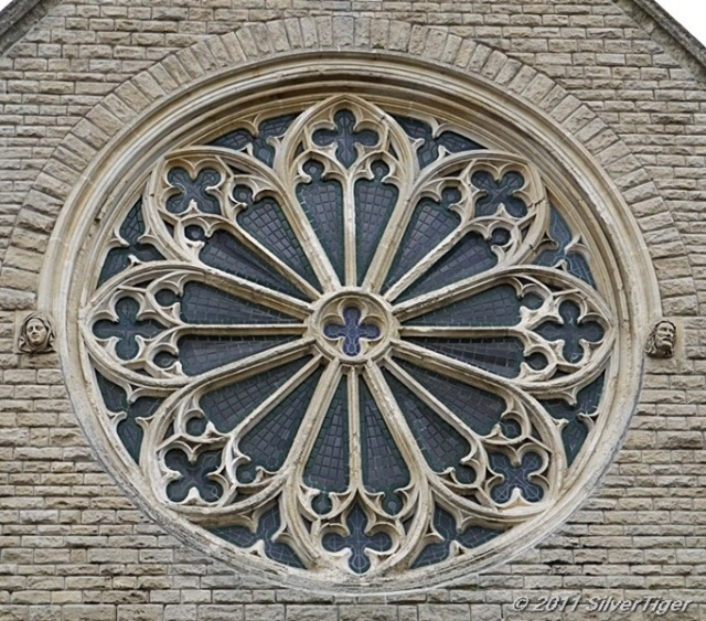 Rose window with carved faces